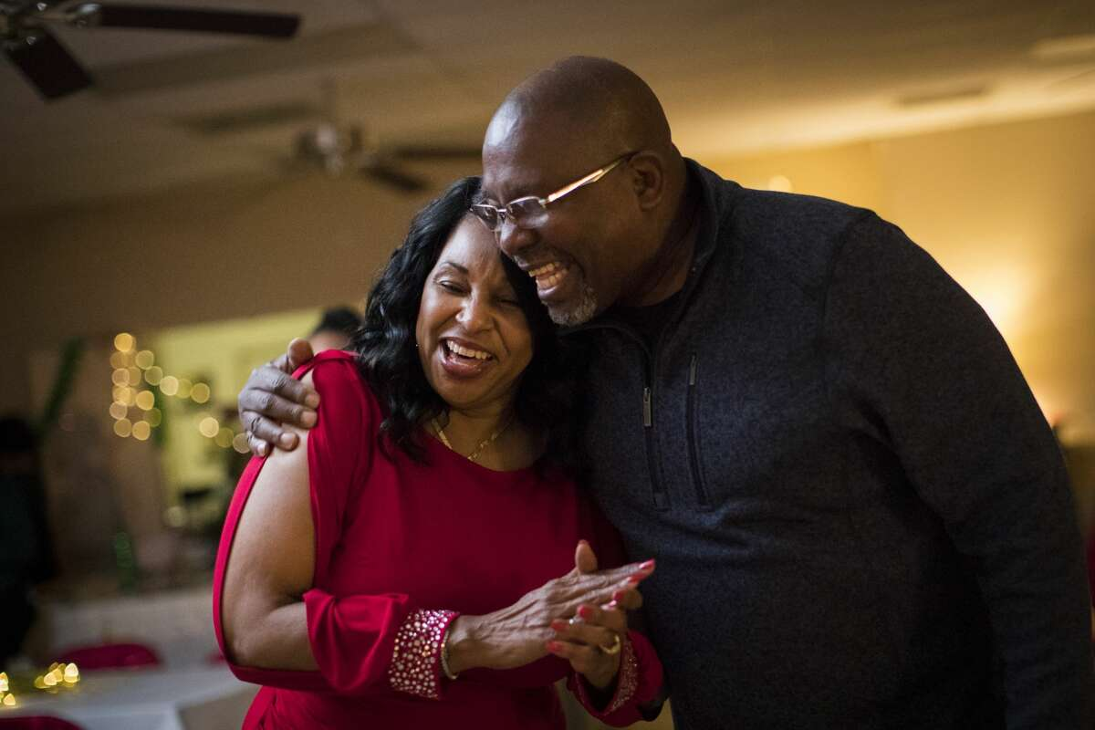Rita Wiltz and Carl White embrace during the Jingle all the Way to Literacy holiday party, Saturday, Dec. 8, 2018, in Tamina. Wiltz is the executive director of Children's Books on Wheels, a non-profit organization based in Tamina that helps families get access to books.
