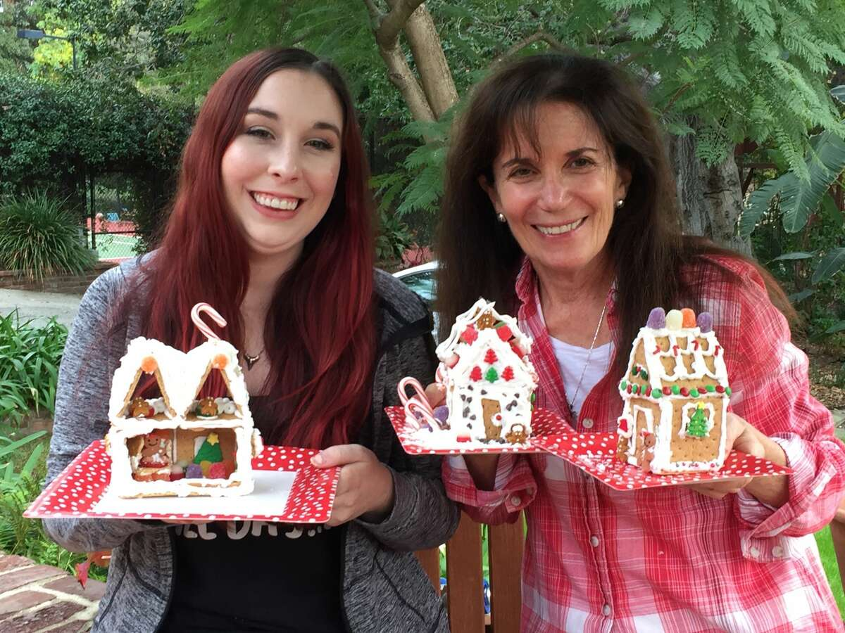 """New tradition: Cathy Guisewite and her daughter, Ivy, pose with """"gingerbread"""" houses made out of graham crackers, icin, and candy. Photo provided"""