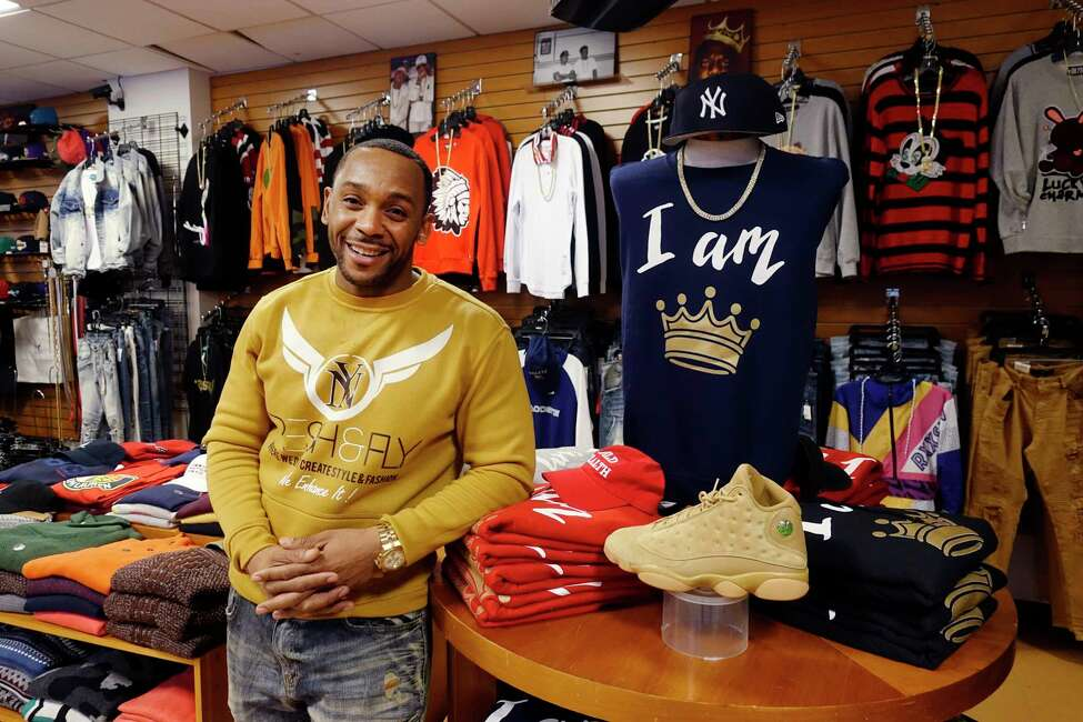 Angelo Maddox, owner of Fresh & Fly, poses inside his store on South Pearl Street next to some of his own clothing designs on Monday, Dec. 17, 2018, in Albany, N.Y. (Paul Buckowski/Times Union)