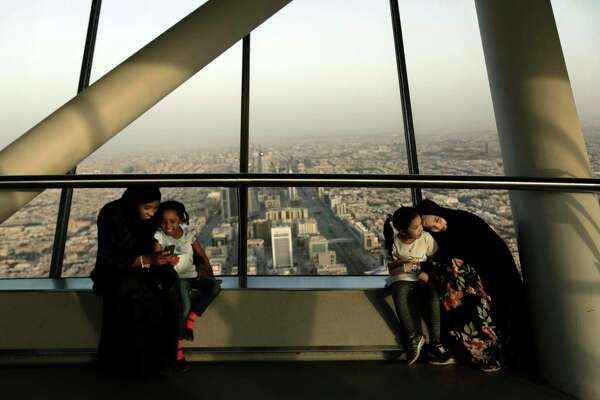 FILE - In this June 23, 2018 file photo, women hold their daughters as they visit the Four Seasons Skyline Tower, in Riyadh, Saudi Arabia. King Salman has extended monthly allowances for government employees, military personnel, pensioners, social security recipients and students into next year. The announcement, carried by the Saudi Press Agency on Tuesday, Dec. 18, 2018, comes on the same day the kingdom's 2019 budget is scheduled to be unveiled.