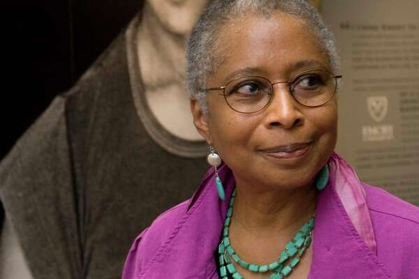 """FILE - In this April 23, 2009 file photo, Alice Walker stands in front of a picture of herself from 1974 as she tours her archives at Emory University, in Atlanta. Walker and The New York Times are drawing fire after she praised an author who critics say is a conspiracy theorist who expresses anti-Semitism. In an interview in Sunday's """"By The Book"""" column, the author of """"The Color Purple"""" said David Icke's 1995 book, """"And The Truth Shall Set You Free,"""" is on her nightstand. A New York Times spokesperson says the column is not a list of recommendations from its editors."""