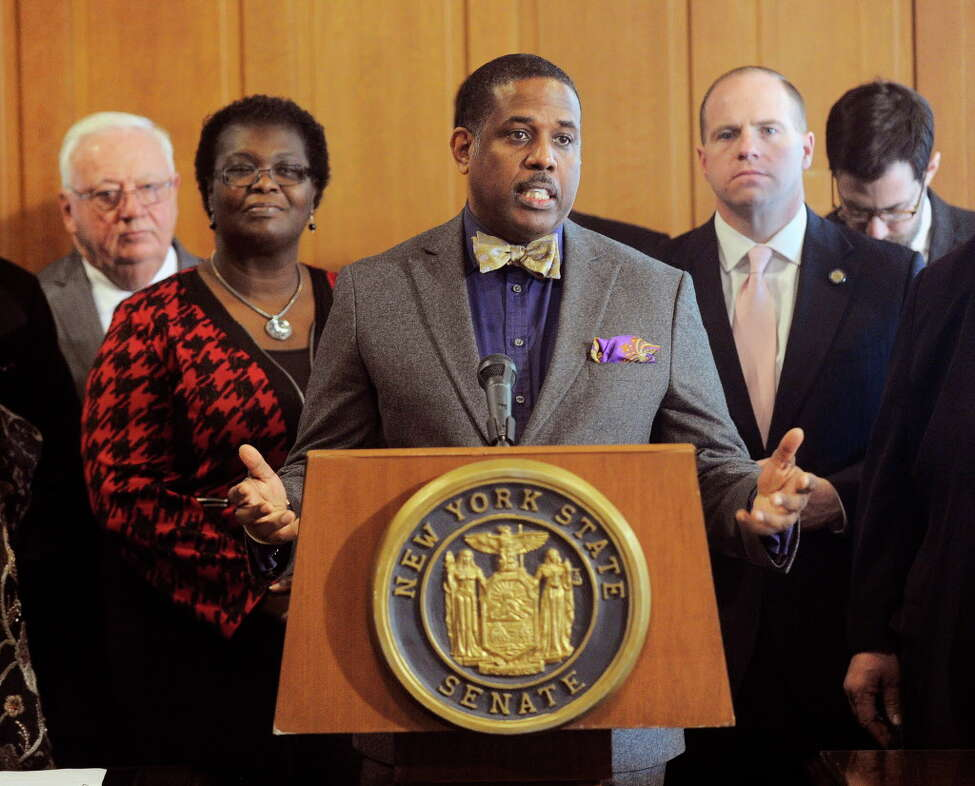 In this Feb. 6, 2017, file photo, Sen. Kevin Parker, D- Brooklyn, stands at the podium, flanked by Senate members during a news conference at the Capitol in Albany, N.Y. Parker wants to require police to scrutinize social media activity and online searches of handgun license applicants, and disqualify those who make violent or hateful posts. The bill's fate is uncertain amid questions from free-speech advocates.