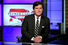 "FILE - In this March 2, 2017, file photo, Tucker Carlson, host of ""Tucker Carlson Tonight,"" poses for photos in a Fox News Channel studio in New York. Some advertisers say they are leaving conservative host Carlson's show following his remarks referring to immigrants as ""the world's poor."" It's the latest example of sponsors leaving a Fox News Channel show after controversy, but experts say the flap is likely to blow over. So far, the biggest advertisers are sticking with him and his show, ""Tucker Carlson Tonight."""