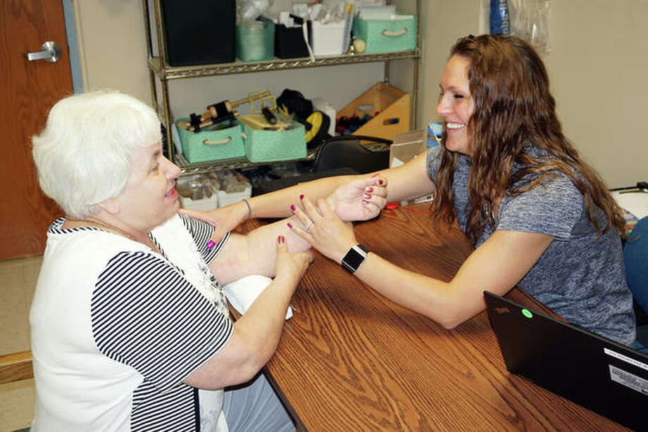 Callie Feldman, an occupational therapist at Alton Memorial Hospital's Human Motion Institute, does some hand therapy with Joanna Krajewski of Wood River. Photo: For The Telegraph