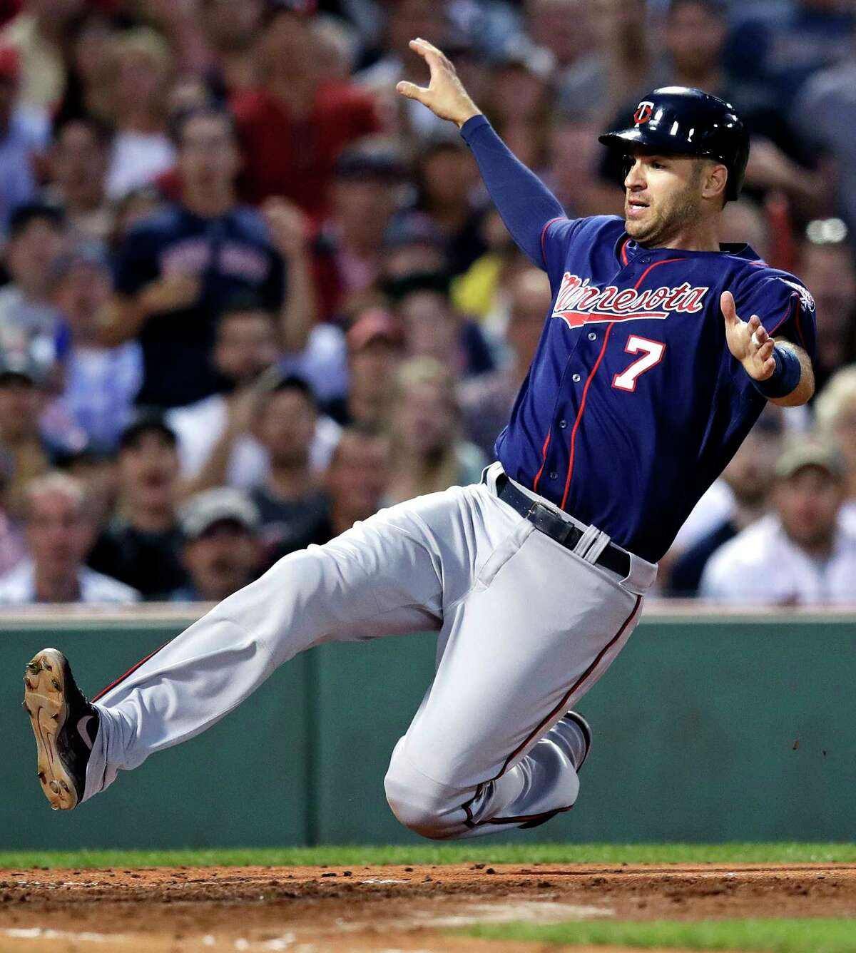 FILE - In this June 29, 2017, file photo, Minnesota Twins' Joe Mauer starts to slide as he scores on a double by Jorge Polanco during the fourth inning of the team's baseball game against the Boston Red Sox, at Fenway Park in Boston. The Minnesota Twins will retire Joe Mauer's No. 7 jersey next season, moving swiftly with the prestigious honor for the six-time All-Star who recently finished a 15-year major league career. The Twins surprised Mauer with the announcement while he was being celebrated at an all-student assembly at his alma mater Cretin-Derham Hall High School on Tuesday, Dec. 18, 2018.
