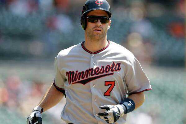FILE - In this July 20, 2016, file photo, Minnesota Twins' Joe Mauer heads home after his solo home run during the first inning of a baseball game against the Detroit Tigers, in Detroit. The Minnesota Twins will retire Joe Mauer's No. 7 jersey next season, moving swiftly with the prestigious honor for the six-time All-Star who recently finished a 15-year major league career. The Twins surprised Mauer with the announcement while he was being celebrated at an all-student assembly at his alma mater Cretin-Derham Hall High School on Tuesday, Dec. 18, 2018.