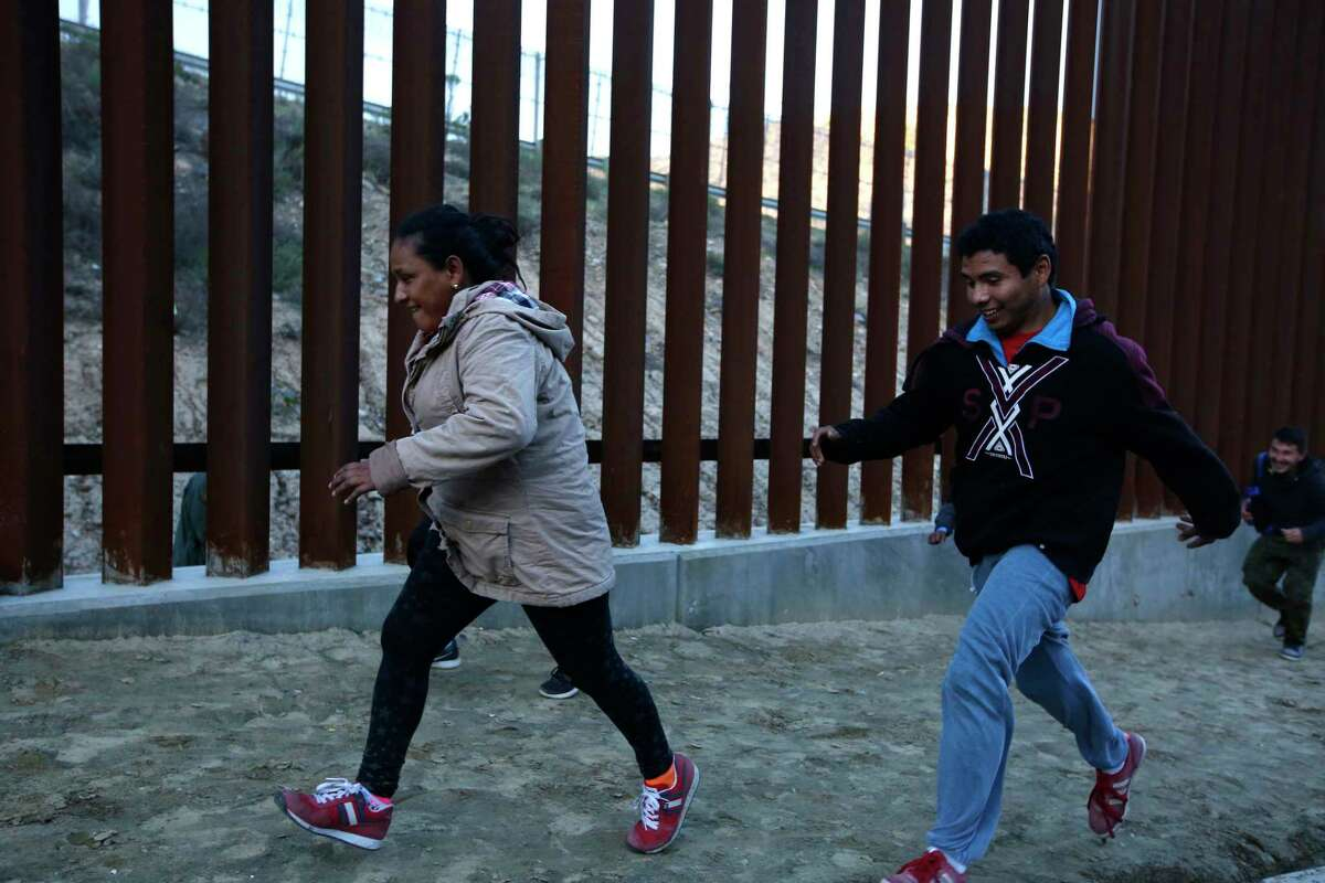 Honduran migrants run away from Border Patrol agents as they try to cross over the U.S. border wall to San Diego, California, from Tijuana, Mexico, Saturday, Dec. 15, 2018.