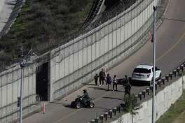 Honduran asylum seekers are taken into custody by U.S. Border Patrol agents after the group crossed the U.S. border wall into San Diego, California, seen from Tijuana, Mexico, Sunday, Dec. 16, 2018.