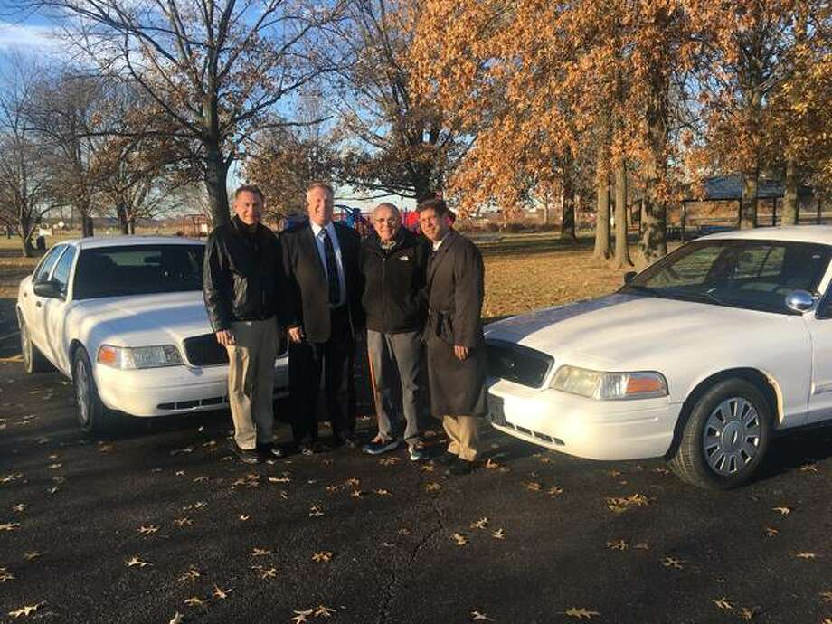 Madison County Board members, from left, Mike Walters and Ray Wesley, and Godfrey Mayor Mike McCormick and Chairman Kurt Prenzler stand with the decommissioned Madison County Sheriff's Department vehicles that the village purchased for $1 each. Photo: For The Telegraph