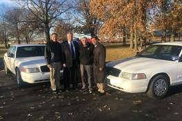 Madison County Board members, from left, Mike Walters and Ray Wesley, and Godfrey Mayor Mike McCormick and Chairman Kurt Prenzler stand with the decommissioned Madison County Sheriff's Department vehicles that the village purchased for $1 each.