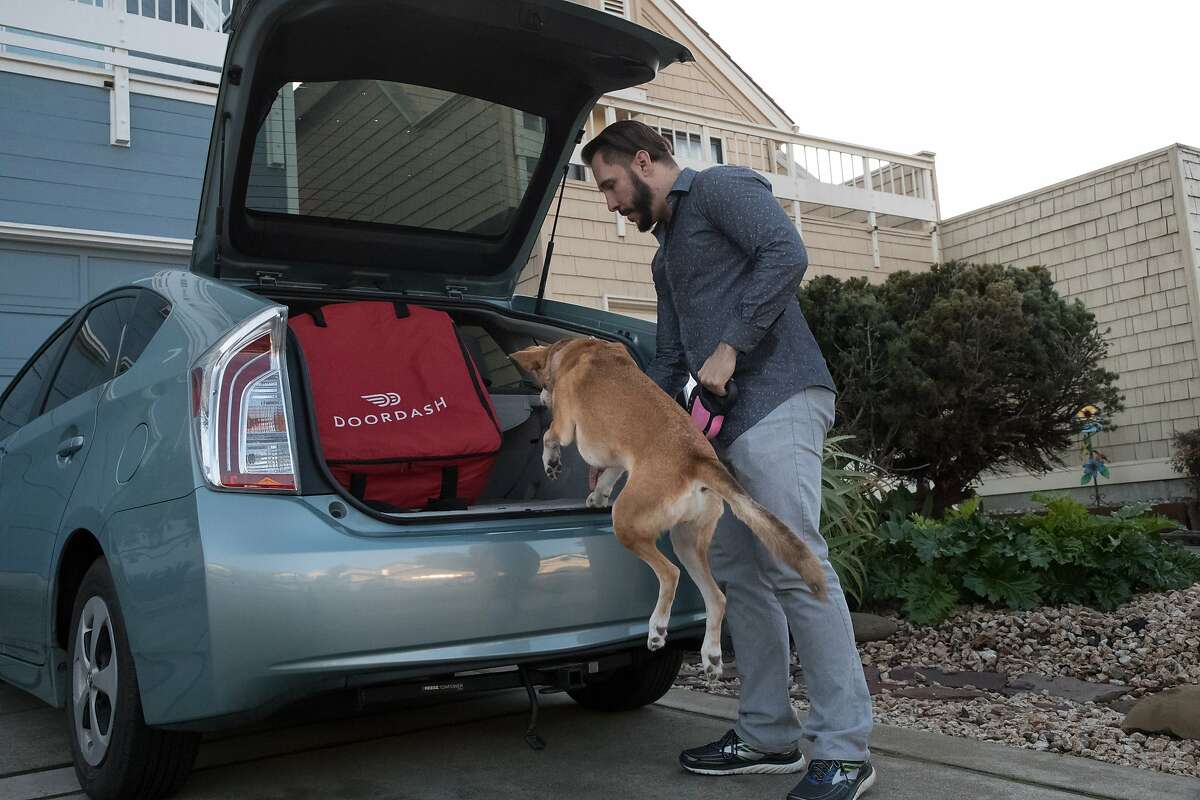 Jon Gallez lets his dog Mia hop into the car and she sits in the passenger seat during Doordash deliverys on Saturday, Dec. 8, 2018, in San Mateo, Calif.