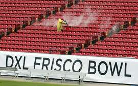 A worker power washes the seating area at Toyota Stadium in Frisco, Texas, Monday, Dec. 17, 2018. San Diego State and Ohio are scheduled to play football in the DXL Frisco Bowl at the venue on Wednesday. (AP Photo/Tony Gutierrez)