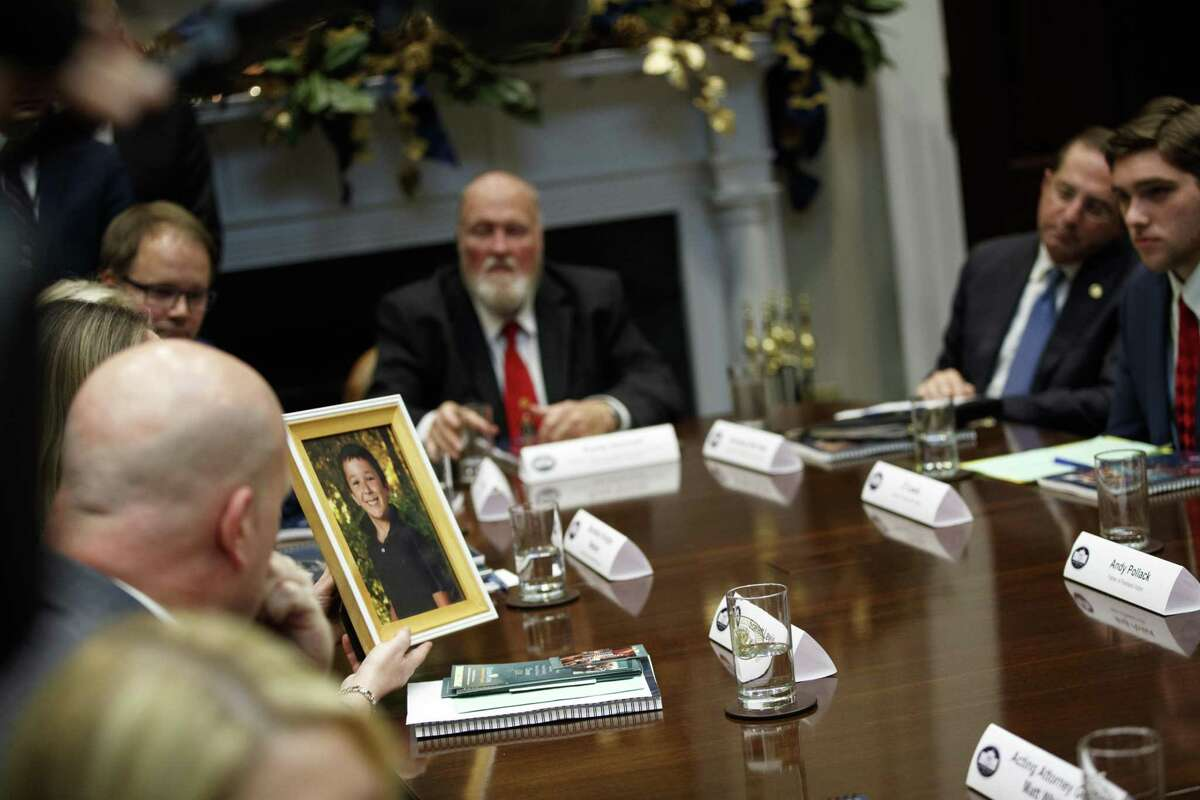 Scarlett Lewis holds up a photo of her son Jesse Lewis, who was killed in the Sandy Hook school shooting, during a meeting with President Donald Trump on the Federal Commission on School Safety report, in the Roosevelt Room of the White House, Tuesday, Dec. 18, 2018, in Washington.