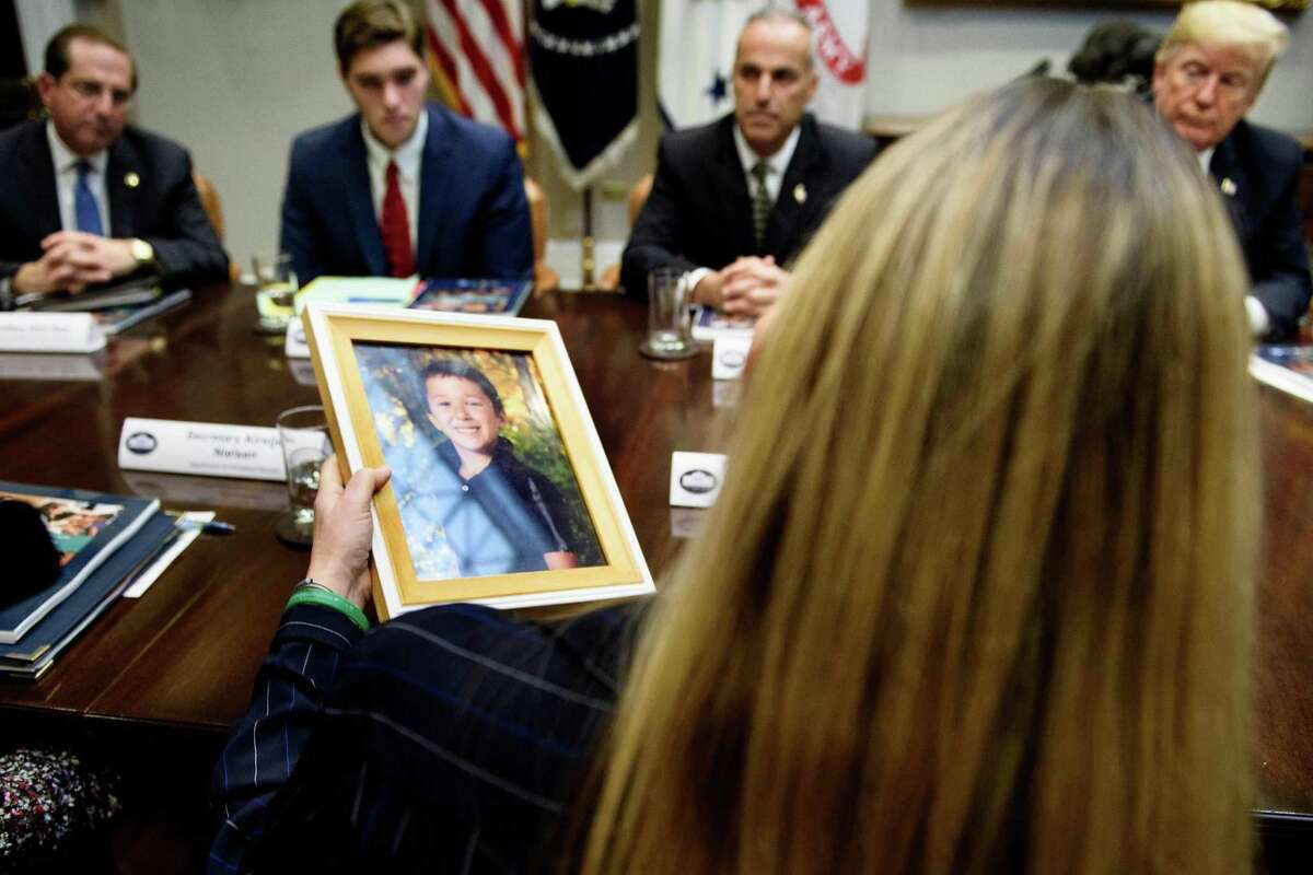 US President Donald Trump and others listen as Scarlett Lewis, holding a photo of her son, Sandy Hook mass shooting victim Jesse Lewis, speaks during a roundtable discussion about school safety in the Roosevelt Room of the the White House December 18, 2018 in Washington, DC.