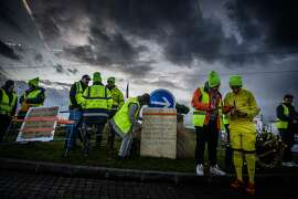 """Yellow vest (Gilets jaunes) protestors occupy a traffic circle Near Feyzin Refinery, on December 17, 2018, central eastern France. - The Yellow vests experiment solidarity and feel like a """"family"""" on the blockade near Feyzin refinery, AFP reported on December 18, 2018. (Photo by JEAN-PHILIPPE KSIAZEK / AFP)JEAN-PHILIPPE KSIAZEK/AFP/Getty Images"""