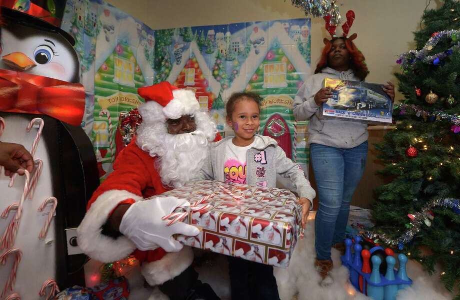 Children including Naliyah DeLeon, 5, visit with Santa, aka James Dupree, and receive a gift during the DDH Hope Foundation Inc. 4th annual Fund A Family Christmas Party event Saturday, December 15, 2018, at the South Norwalk Community Center. Over a hundred needy children were served during the annual event. Photo: Erik Trautmann / Hearst Connecticut Media / Norwalk Hour