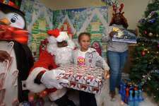 Children including Naliyah DeLeon, 5, visit with Santa, aka James Dupree, and receive a gift during the DDH Hope Foundation Inc. 4th annual Fund A Family Christmas Party event Saturday, December 15, 2018, at the South Norwalk Community Center. Over a hundred needy children were served during the annual event.