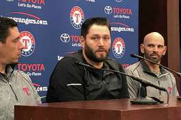 Newly signed Texas Rangers pitcher, Lance Lynn, center, responds to reporters questions as team general manager Jon Daniels, left, and manager Chris Woodward, right, look on in Arlington, Texas, Tuesday, Dec. 18, 2018.