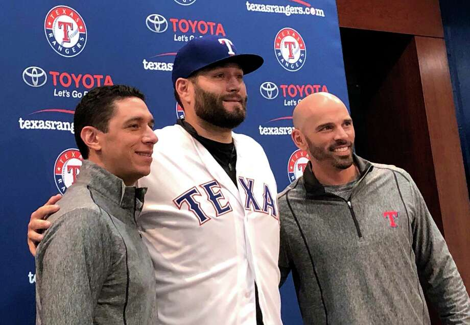 Newly signed Texas Rangers pitcher, Lance Lynn, center, wears his new team jersey as he poses for photos with general manager Jon Daniels, left, and manager Chris Woodward, right, after a news conference where Lynn was officially introduced in Arlington, Texas, Tuesday, Dec. 18, 2018. Photo: Stephen Hawkins, AP / Copyright 2018 The Associated Press. All rights reserved.
