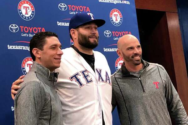 Newly signed Texas Rangers pitcher, Lance Lynn, center, wears his new team jersey as he poses for photos with general manager Jon Daniels, left, and manager Chris Woodward, right, after a news conference where Lynn was officially introduced in Arlington, Texas, Tuesday, Dec. 18, 2018.