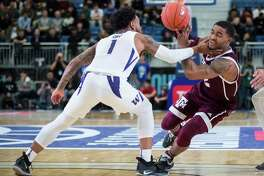 Texas A&M Aggies' TJ Starks, right, drives to the basket past Washington Huskies' David Crisp during the first half of an NCAA college basketball game in Vancouver, Tuesday, Nov. 20, 2018. (Darryl Dyck/The Canadian Press via AP)