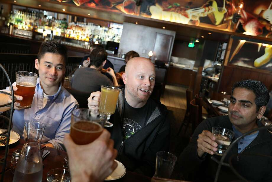 Mark Williamson (center) gives a toast to staff at a holiday office party with Charles Taira (left), Jeevan Balani (right) and others at Zero Zero in San Francisco. Photo: Lea Suzuki / The Chronicle