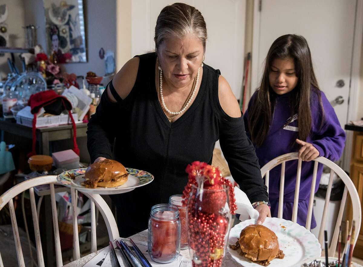 Elisa Barragan prepares dinner for herself and her nine-year-old granddaughter, Khloe Barragan, at their home in San Jose, Calif. Tuesday, Dec. 11, 2018.