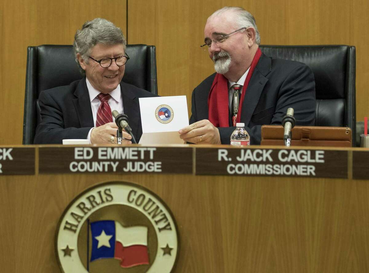 Former Harris County Judge Ed Emmett, left, and Precinct 4 Commissioner R. Jack Cagle take a look at a card during Emmett's last Commissioners Court meeting Dec. 18, 2018, in Houston.