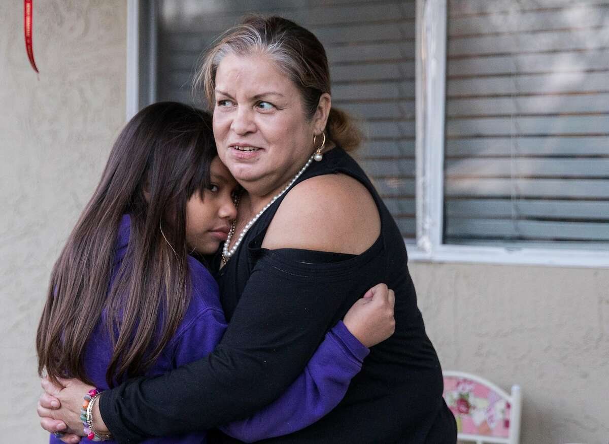 Elisa Barragan and her nine-year-old granddaughter, Khloe Barragan, embrace on the front porch of their home in San Jose, Calif. Tuesday, Dec. 11, 2018.