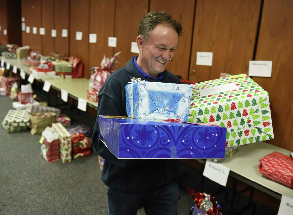 Longtime volunteer Fernando Ruiz distributes gifts to families at Town Hall in Greenwich, Conn. Tuesday, Dec. 18, 2018. The Department of Human Services' Angel Tree program has been collecting and distributing holiday gifts to low income families in a tradition that goes back 25 years. Both demand and donation numbers increased this year as 223 families in need were given more than 750 gifts through the program.