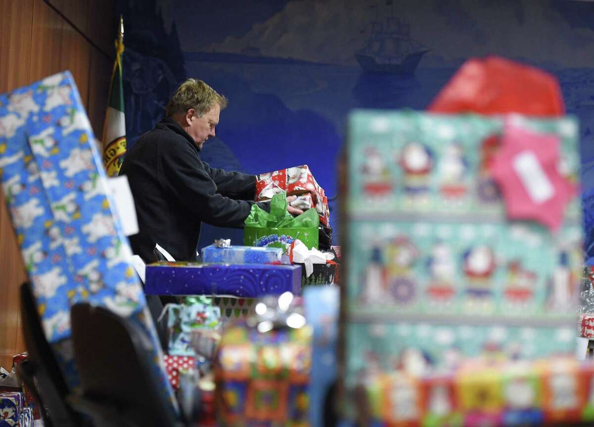 Volunteer Roderick Brush collects gifts to distribute to families at Town Hall in Greenwich, Conn. Tuesday, Dec. 18, 2018. The Department of Human Services' Angel Tree program has been collecting and distributing holiday gifts to low income families in a tradition that goes back 25 years. Both demand and donation numbers increased this year as 223 families in need were given more than 750 gifts through the program.
