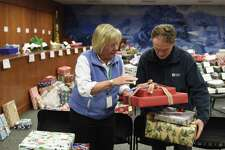 Department of Human Services Community Gift Program Coordinator Alison Brush and longtime volunteer Fernando Ruiz collect gifts to distribute to families at Town Hall in Greenwich, Conn. Tuesday, Dec. 18, 2018. The Department of Human Services' Angel Tree program has been collecting and distributing holiday gifts to low income families in a tradition that goes back 25 years. Both demand and donation numbers increased this year as 223 families in need were given more than 750 gifts through the program.
