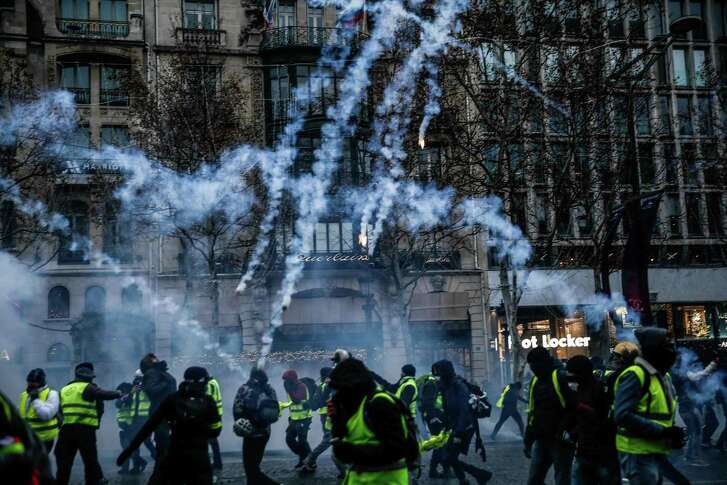 Protesters wearing yellow vests stand amid smoke of tear gas during a demonstration against rising costs of living they blame on high taxes on the Champs-Elysees avenue in Paris, on December 15. These protests illustrate a trend in other Western countries as well — outsiders, often in the less metropolitan areas, against the urban elites.