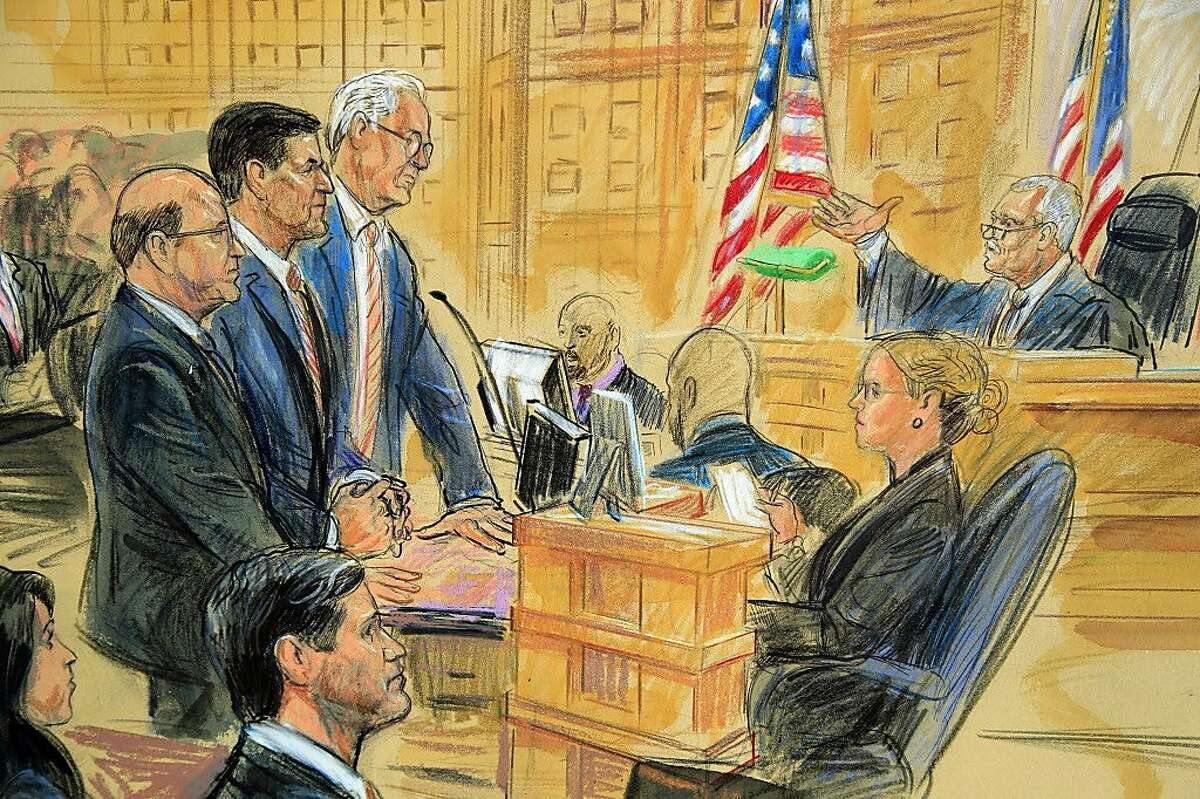 This courtroom sketch depicts former President Donald Trump's former national security adviser Michael Flynn, standing center, flanked by his lawyers, listening to U.S. District Judge Emmet Sullivan, right, as he addresses Flynn and points to the American flag inside the federal court in Washington, Washington, Tuesday, Dec. 18, 2018.