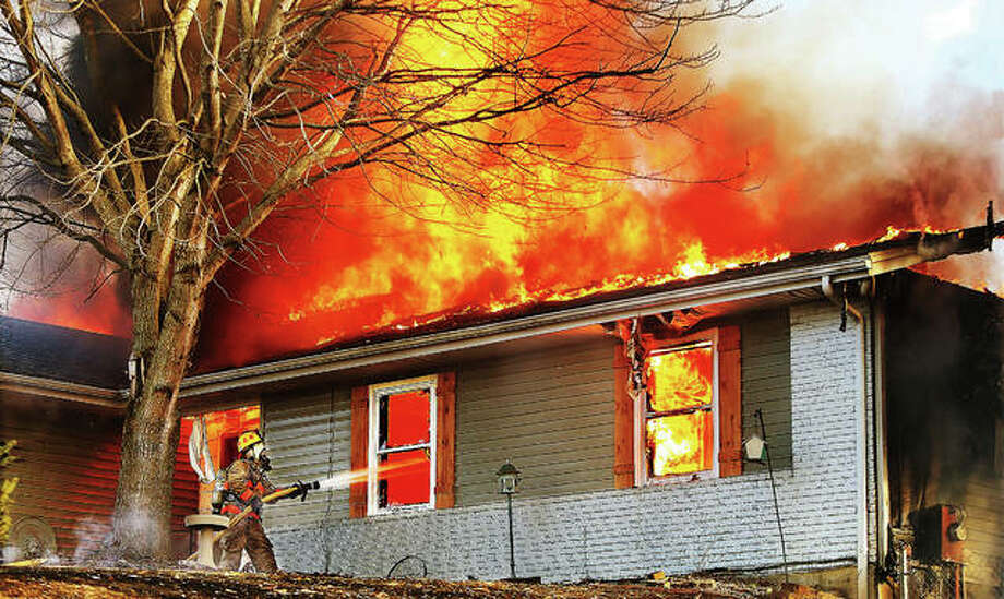 A firefighter directs a hose line through the window of a house Tuesday afternoon in the 4800 block of Rocky Branch Road in rural Dorsey as flames consume the roof and contents of the house. Smoke from the fire was visible from the east side of Alton. Firefighters from Dorsey, Fosterburg, Holiday Shores, Bunker Hill, Prairetown and Bethalto battled the fire but the house was a total loss. No injuries were reported. Photo: John Badman | For The Telegraph