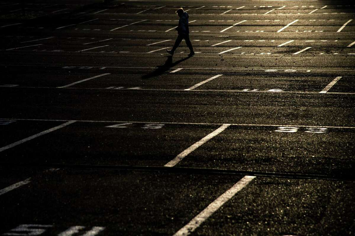 TOPSHOT - A person walks across an empty parking lot at sunset in Turin on November 27, 2018. (Photo by MARCO BERTORELLO / AFP)MARCO BERTORELLO/AFP/Getty Images