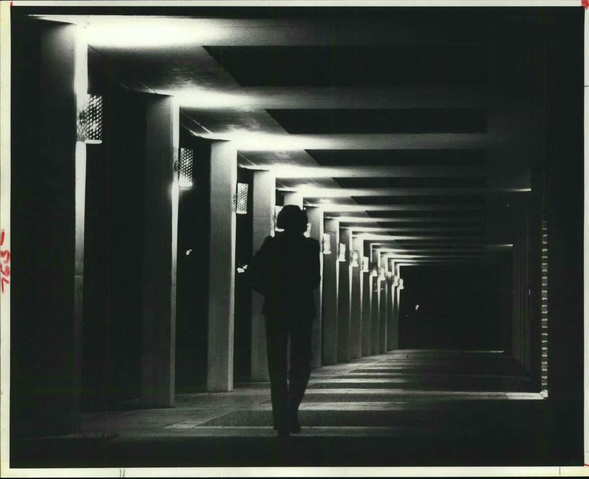 Houston Baptist University. The lights outside Sharp Gymnasium at Houston Baptist University offer stark contrast as a student, her arms loaded with books, takes a solitary walk after an evening of study. Hallway outside Sharp Gym on HBU campus.