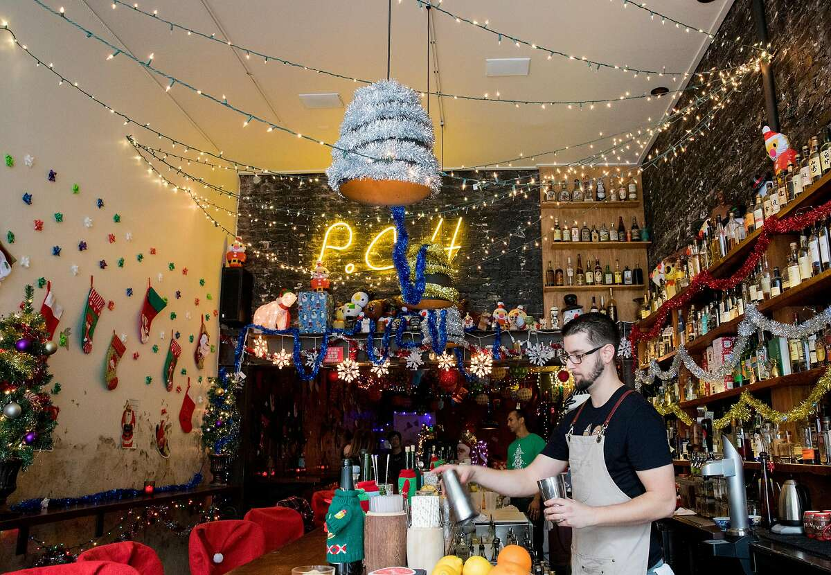 """Bartender Sam Carlisi drinks behind the bar of Pacific Cocktail Haven's Christmas-themed pop-up called """"Miracle"""" in San Francisco, Calif. Tuesday, Dec. 18, 2018."""