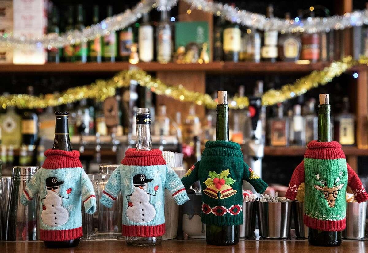 Liquor bottles are seen adorned in Christmas sweaters on the bar of Pacific Cocktail Haven's Christmas-themed pop-up called