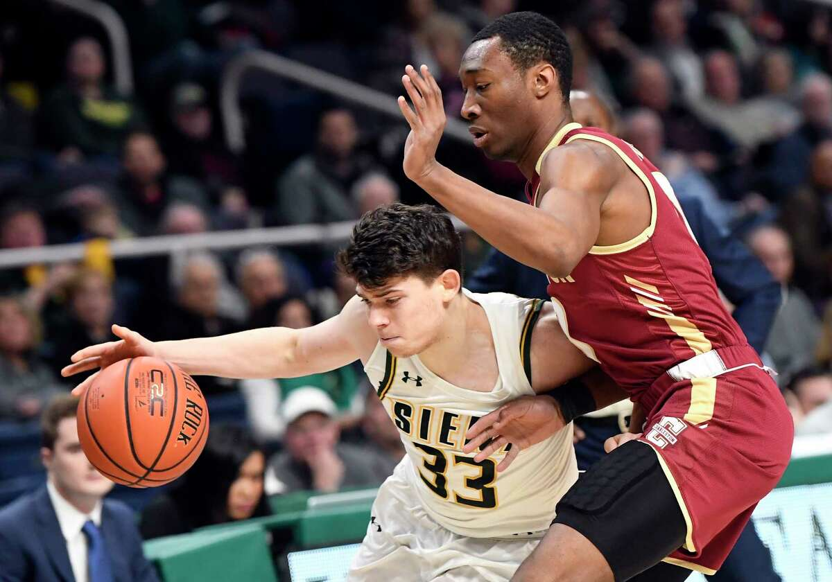 Siena guard Georges Darwiche (33) moves the ball past Charleston guard Jaylen Richard (0) in the first half of an NCAA college basketball game in Albany, N.Y., Tuesday, Dec. 18, 2018. Charlston won the game 83-58.