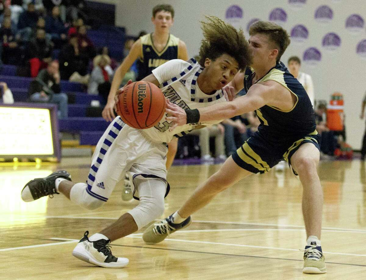 Lake Creek point guard Pierce Spencer (5) knocks the ball away from Willis point guard D?'Shawn Woods (13) during the second quarter of a District 20-5A high school basketball game at Willis High School, Tuesday, Dec. 18, 2018, in Willis.