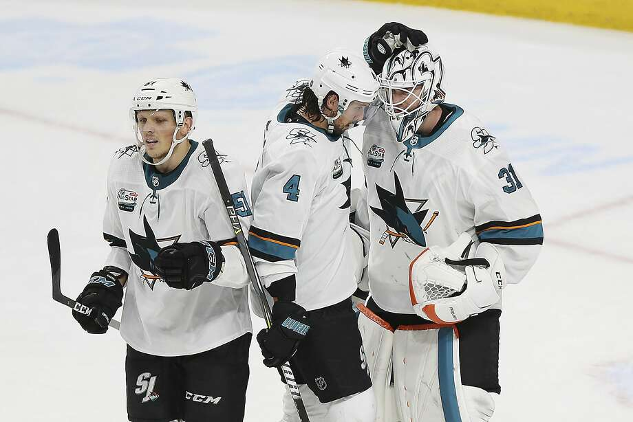 Defenseman Brenden Dillon (4) congratulates goaltender Martin Jones after San Jose won 4-0 against the Minnesota Wild in St. Paul, Minn. At left is rookie defenseman Radim Simek. Photo: Stacy Bengs / Associated Press