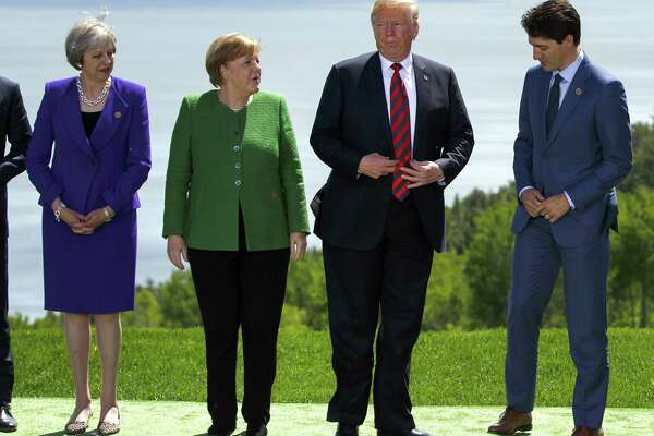 Theresa May, U.K. prime minister, from left, Angela Merkel, Germany's chancellor, U.S. President Donald Trump, and Justin Trudeau, Canada's prime minister, get in place for a family photograph during the Group of Seven (G7) Leaders Summit in La Malbaie, Quebec, on June 8, 2018.