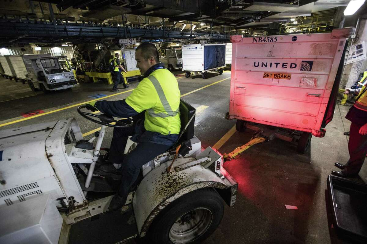 Baggage employees work transfering bags to aircraft at George Bush Intercontinental Airport on Monday, Dec. 17, 2018, in Houston. United Airlines is building a new baggage system in Houston, scheduled to be fully operational in 2022.