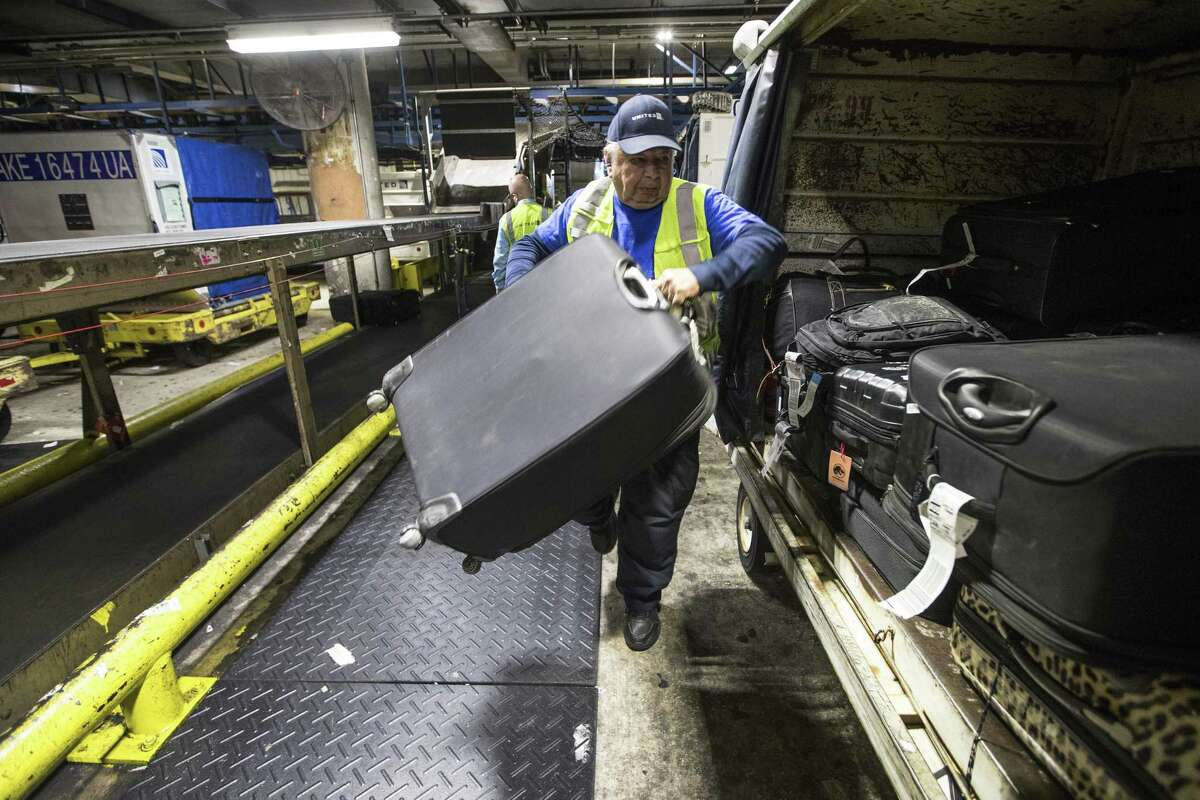 Juan De La Mora works in the bag room transfering luggage to a cart at George Bush Intercontinental Airport on Monday, Dec. 17, 2018, in Houston. United Airlines is building a new baggage system in Houston, scheduled to be fully operational in 2022.