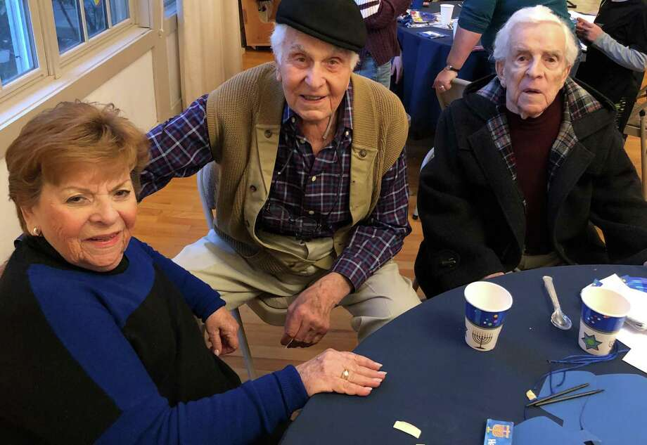 Jewish Community Center in Sherman founders, from left to right, Rochelle Etingin, David Marks and Maks Etingin, enjoy the festivities at the center's recent Hanukkah party. Photo: Courtesy Of JCC In Sherman / The News-Times Contributed
