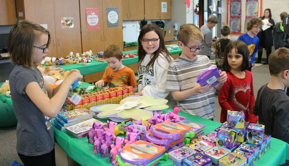 Laker fourth grader Olivia Redmond (left) answers questions about gift products for sale at the table in Santa's Workshop, set up for Laker Elementary students to do some shopping for family members — and themselves, if they wish. Fourth and fifth graders helped with the workshop and with wrapping the gifts purchased. The older students helped as personal shoppers to help the younger students find presents. Pictured here, kindergartner Jasper Kester is being assisted by fourth grader Jaizsmen Guza, and fourth grader Teagon Yurkovich assists kindergartner Addison Talaski. Photo: Submitted Photo