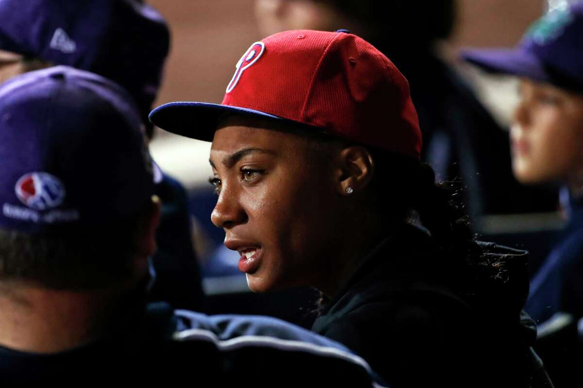 FILE - In this Aug. 19, 2018, file photo, Philadelphia Phillies fan Mo'ne Davis, center, who threw a shutout against Tennessee while competing in the 2014 Little League World Series tournament, talks with members of this year's team from Panama, at the Little League Classic baseball game between the Philadelphia Phillies and the New York Mets, in Williamsport, Pa. Davis, the first girl to pitch a victory in the Little League World Series, will attend Hampton University and play softball.