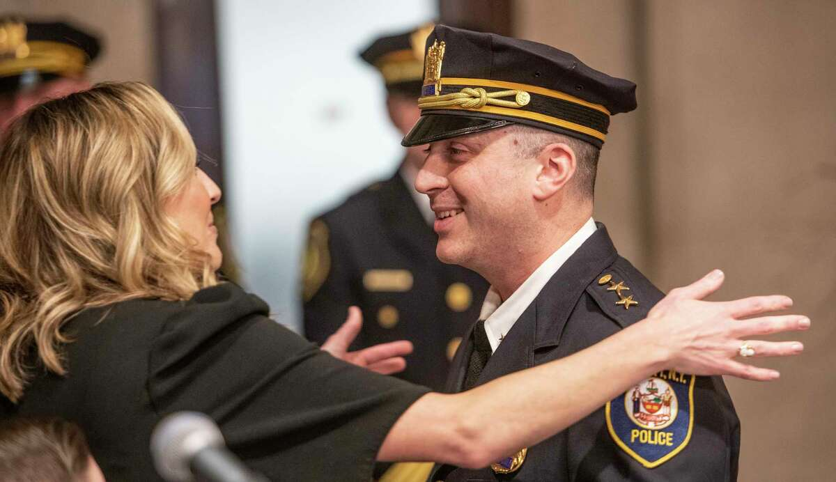 Kristin Donohue, left gives her now deputy chief husband Edward Donohue a big hug during a promotion ceremony held at City Hall Wednesday Dec. 18, 2018 in Albany N.Y. (Skip Dickstein/Times Union)
