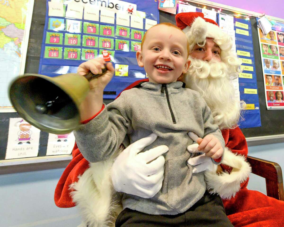 Santa a.k.a Rafael Levy-Lesko has student Lorenzo Gonzalez ring his bell as he makes a visit to teacher Jami Sousis' Pre School Class at A Child's Place, Unity House Wednesday Dec. 18, 2018 in Troyi, N.Y. (Skip Dickstein/Times Union)